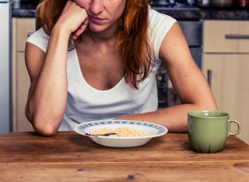 La mujer parece aburrida mirando un tazón de cereal que no es saludable para bajar de peso