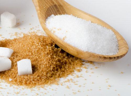 El azúcar blanco en una cuchara de madera se coloca encima del azúcar morena, una pérdida de peso no saludable.