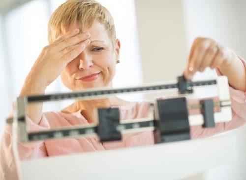 Mujer infeliz en las escalas - pérdida de peso poco saludable