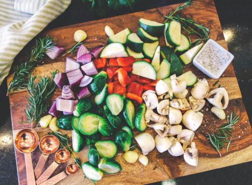 Cocinar de Verduras picadas coles de Bruselas cebollas champiñones pimienta calabaza sobre una tabla de madera - pérdida de peso poco saludable