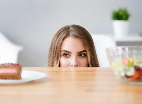 Mujer hambrienta con comida chatarra frente a ensalada - pérdida de peso poco saludable